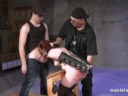 Two dungeon masters spanking their sex slaves