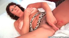 Busty grandma rubs and fingers her hairy cunt