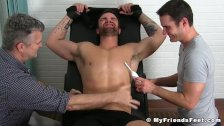 Two pervs tickling body of tied up jock