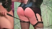 Blonde Mistress in sexy outfit punishing a sissy crossdresser's ass